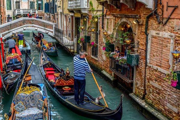 Besuchen Sie die Hauptattraktionen von Venedig, beginnend mit dem Markusplatz und dem Markusdom - dem bedeutenden religiösen Tempel und bekanntesten Beispiel italienisch-byzantinischer Architektur, während Sie am Glockenturm des Markusdoms und den Procuratien vorbeigehen.